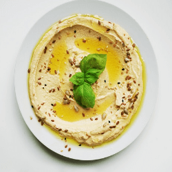 Hummus This wonderful snack food is made from ground chickpeas, olive oil, lemon juice, and garlic. It has a number of awesome trace minerals, is high in protein, and is full of healthy fats that promote heart health. It can be flavored in a variety of ways and comes with the added bonus that they can lower your cholesterol, and contain natural chemicals that can help fight cancer-causing damage.
